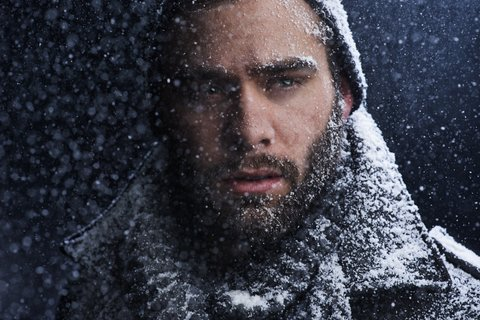 Cropped shot of a serious young man covered in snow in the dark