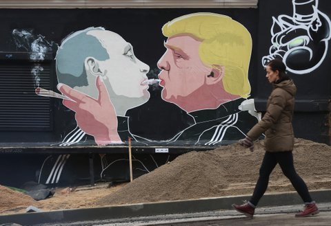 VILNIUS, LITHUANIA - NOVEMBER 23: A woman walks past a mural showing U.S. President-elect Donald Trump (R) blowing marijuana smoke into the mouth of Russian President Vladimir Putin on the wall of a bar-b-que restaurant on November 23, 2016 in Vilnius, Lithuania. Many people in the three Baltic nations of Lithuania, Latvia and Estonia are concerned that Russia, because Trump has expressed both admiration for Putin and doubt over defending NATO member states, will be emboldened to intervene militarily in the Baltics. (Photo by Sean Gallup/Getty Images)