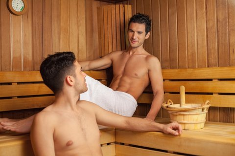 Two young men relaxing in sauna.