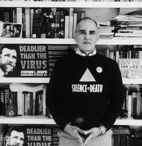 20th December 1989:  Portrait of American author, AIDS campaigner and gay rights activist Larry Kramer, founder of ACT-UP and the Gay Men's Health Crisis group, posing in front of a book shelf in his home, New York City. Kramer is wearing a 'SILENCE = DEATH' T-shirt.  (Photo by Sara Krulwich/New York Times Co./Getty Images)
