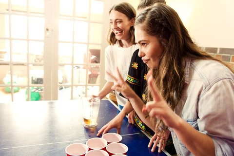 Three girls playing beer pong. One cheering doing hands signals for two with both hands.