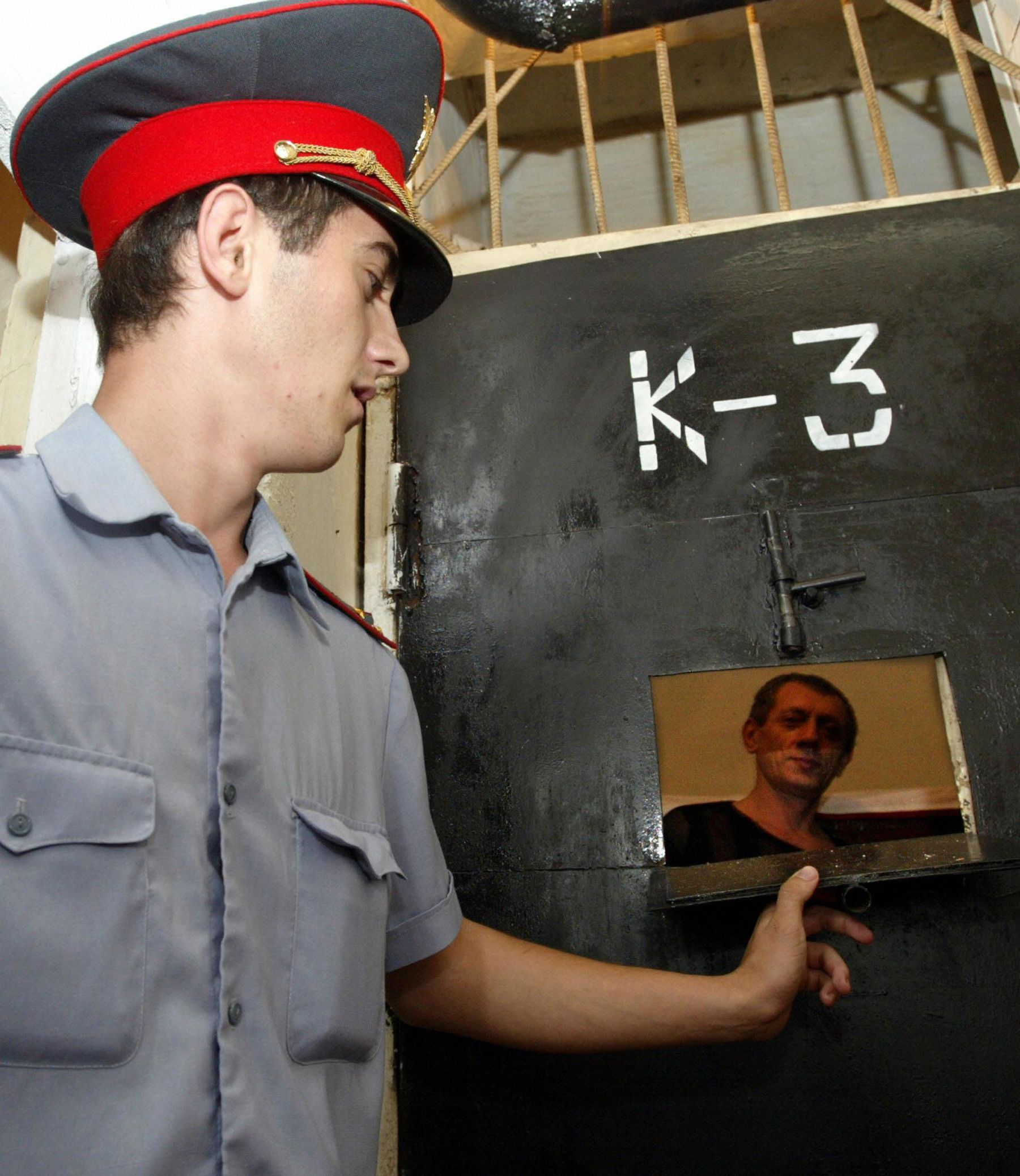 A Chechen policeman looks into the cell in one of the prisons in Grozny, 26 August 2003, at a suspected murderer.    (Photo credit should read ALEXANDER NEMENOV/AFP/Getty Images)