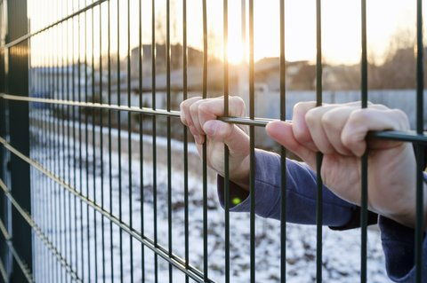 The hands hold onto the metal fence in the rays of the setting sun in winter