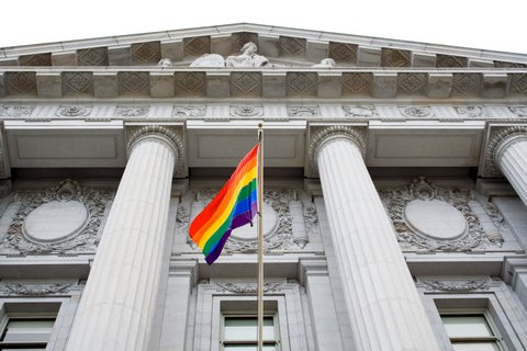 Lesbian, gay, bisexual, and transgender pride flag flying outside a government building