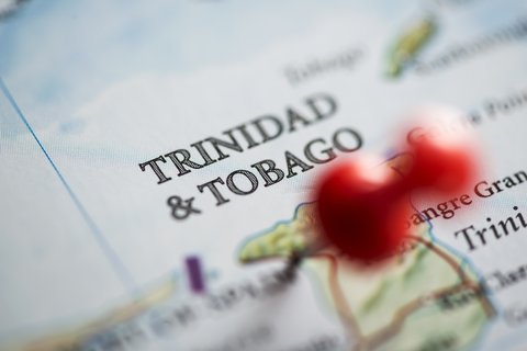 Close up shot of a map. Trinidad and Tobago pinned with a red pushpin.