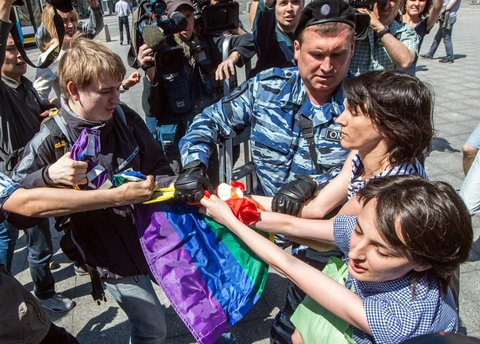 A man (L) takes away a rainbow flag as a policeman detain gay rights activists during their protest in central Moscow on May 31, 2014. Riot police on May 31 arrested two women as a small group of gay rights activists tried to stage a rally in central Moscow dedicated to Conchita Wurst, the bearded Austrian transvestite who won this year's Eurovision song contest. AFP PHOTO / DMITRY SEREBRYAKOV (Photo credit should read DMITRY SEREBRYAKOV/AFP/Getty Images)