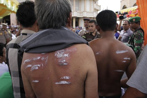 ACEH, INDONESIA - FEBRUARY 12: The injureies of a whipped person are treated with salve during the whipping punishment in front of public at Meulaboh on February 12, 2016 in West Aceh, Indonesia.  About 32 men in Aceh were publicly whipped on Friday as punishment for gambling, a violation of Islamic Sharia law as practiced in Indonesia's semi-autonomous province of Aceh on Sumatra Island. PHOTOGRAPH BY Jefta Images / Barcroft Media UK Office, London. T +44 845 370 2233 W www.barcroftmedia.com USA Office, New York City. T +1 212 796 2458 W www.barcroftusa.com Indian Office, Delhi. T +91 11 4053 2429 W www.barcroftindia.com (Photo credit should read Jefta Images / Barcroft Media / Barcroft Media via Getty Images)