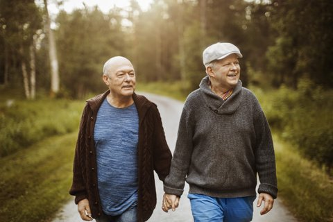 Happy gay couple looking away while walking on road amidst trees