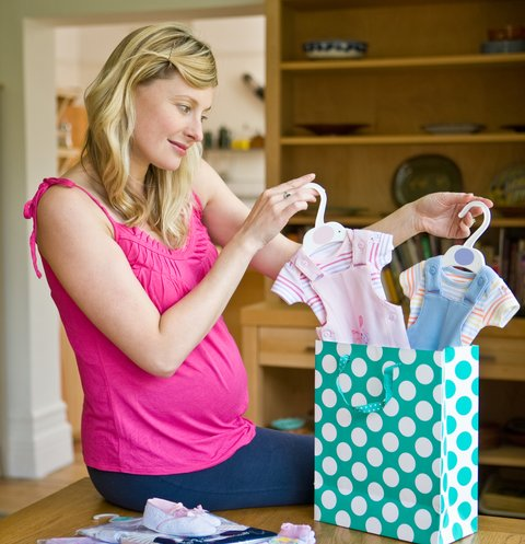 Pregnant woman, late twenties, unpacking baby clothes from shopping bag.