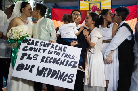 MANILA, PHILIPPINES - JUNE 28:  Filipino LGBT (Lesbian, Gay,Bisexual, Transgender) couples hold a placard and kiss their partners during a mass 'wedding rites' on June 28, 2015 in Manila, Philippines. A small Christian ecumenical group officiated the wedding of one gay and 14 lesbian couples in simple ceremony rites held in a basketball court in the middle class district of Quezon City. Same sex marriage unions are not officially recognized under Philippine laws and is staunchly rejected by the dominant Catholic church in the Philippines. Organizers said todays rites had a special relevance following the landmark U.S. Supreme Court ruling on gay marriage and emboldens other countries to adopt a more tolerant stance on same sex unions.  (Photo by Dondi Tawatao/Getty Images)