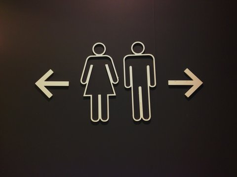 Sign of public restroom on black background