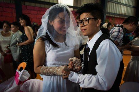 MANILA, PHILIPPINES - JUNE 28:  A Filipino LGBT (Lesbian, Gay,Bisexual, Transgender) couple exchange 'Rite of Holy Union' vows during mass 'wedding rites' on June 28, 2015 in Manila, Philippines. A small Christian ecumenical group officiated the wedding of one gay and 14 lesbian couples in simple ceremony rites held in a basketball court in the middle class district of Quezon City. Same sex marriage unions are not officially recognized under Philippine laws and is staunchly rejected by the dominant Catholic church in the Philippines. Organizers said todays rites had a special relevance following the landmark U.S. Supreme Court ruling on gay marriage.  (Photo by Dondi Tawatao/Getty Images)